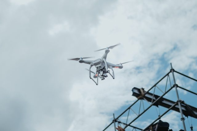 drone flying past building